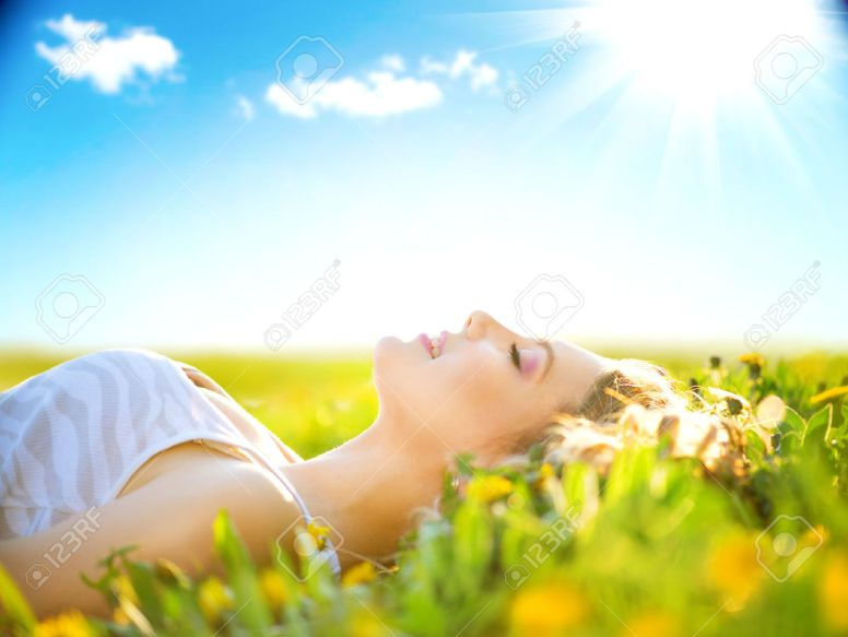 39523241-Beautiful-healthy-girl-lying-on-summer-field-with-flowers-Stock-Photo